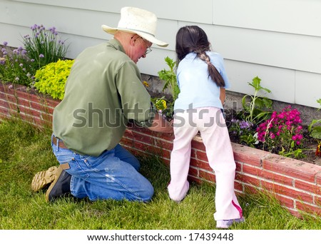 A young child is helping her Grandfather in the garden - stock photo