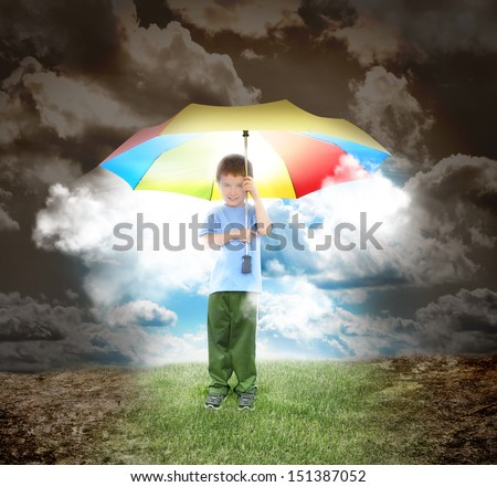 A young child is holding a rainbow umbrella with sunshine glowing out. The boy is surrounded with a dried up landscape and grass under his shoes for a home concept. - stock photo