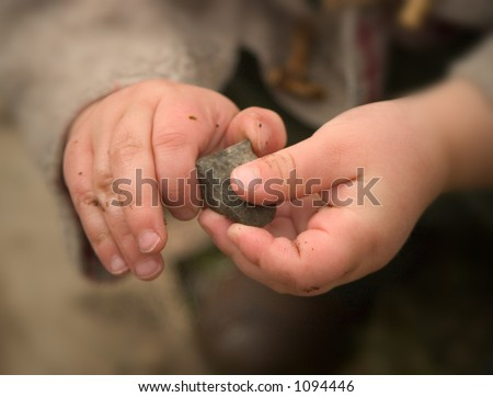 A young child is holding and playing with a small stone - stock photo