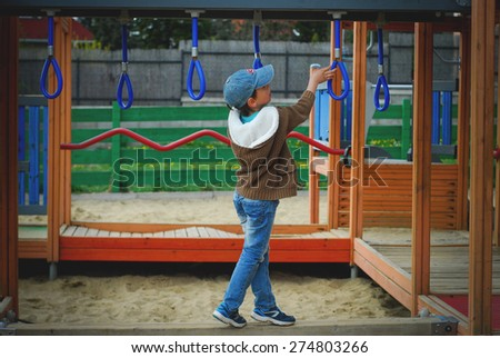 A young child playing at a playground. - stock photo