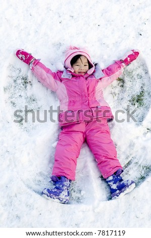 A young child playing in the snow making an angle - stock photo
