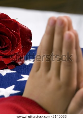 A young child prays for a fallen loved one. In the background is a folded flag and red rose. - stock photo