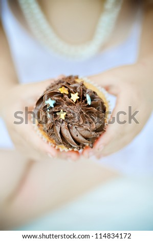 A young child's hands holding chocolate cupcake - stock photo