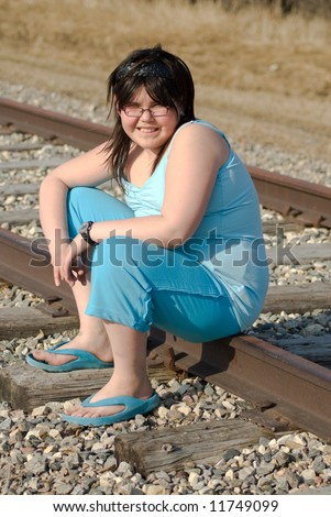 A young child smiling while she's sitting on the railroad tracks - stock photo