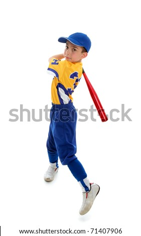 A young child wearing a baseball or softball uniform swinging a bat on a white background. - stock photo