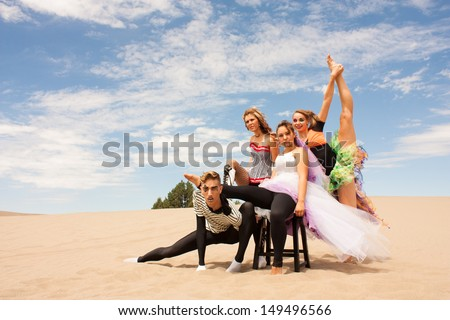 A young circus troupe balance, supporting each other on the desert sand - stock photo