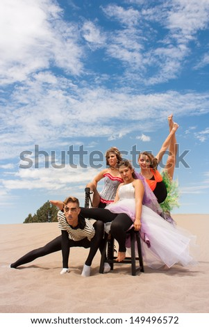 A young circus troupe pose supporting one another in the desert sand - stock photo