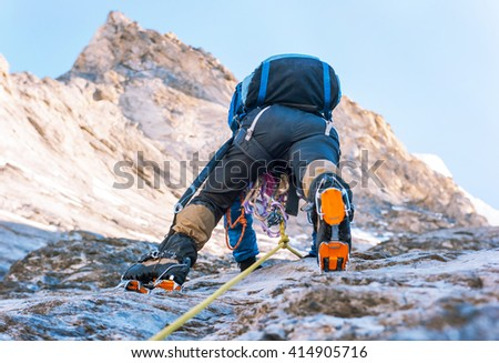 A young climbers reaching the summit. Extreme sport concept - stock photo