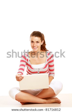 A young colledge girl sitting on the floor with a laptop, isolated on white - stock photo