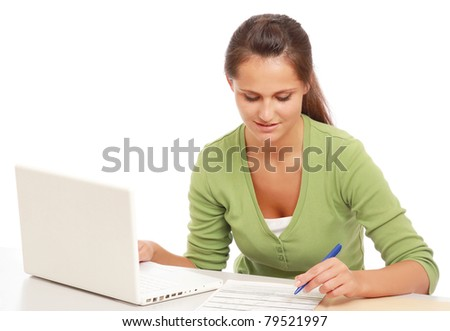 A young college girl studying in front of a laptop, isolated on white - stock photo