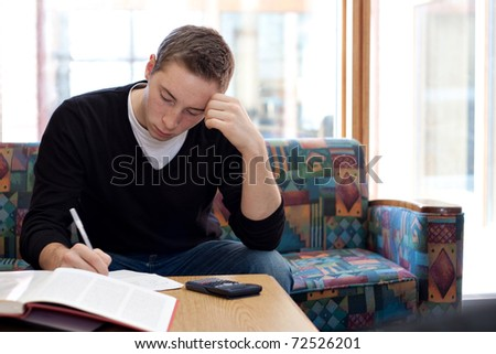 A young college student cramming before his final exams. - stock photo