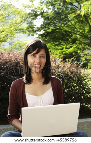 A young college student with a laptop at a public park