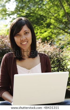 A young college student with a laptop in a park - stock photo