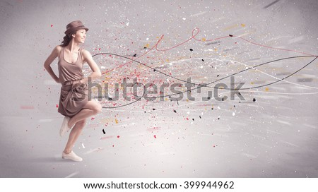A young contemporary energetic dancer in action in front of a grey wall background with lines, spray dots and splatter concept - stock photo