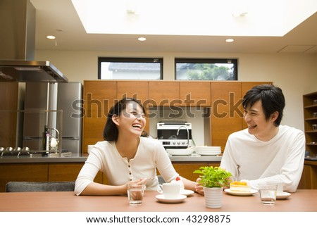 A young couple chatting and laughing in the kitchen - stock photo