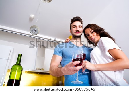 A young couple drinking wine in the kitchen at home. - stock photo
