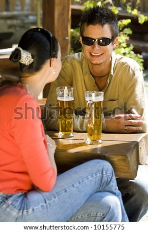 A young couple enjoying a glass of beer with each other - stock photo