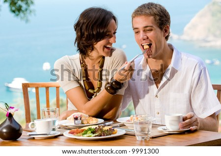 A young couple enjoying breakfast outside with an ocean backdrop - stock photo
