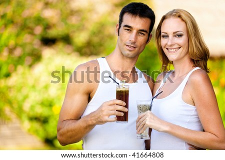 A young couple enjoying drinks together outdoors