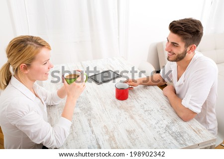 A young couple flirting and having a coffee.  - stock photo