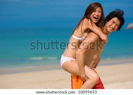 A young couple having fun on a tropical beach - stock photo
