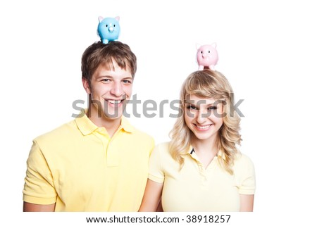 A young couple holding a piggy bank on their heads, can be used for finance or saving concept - stock photo
