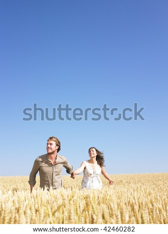 A young couple holding hands and walking through wheat field. Vertically framed shot. - stock photo