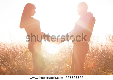 A young couple holding hands on the nature of the bright sun - stock photo