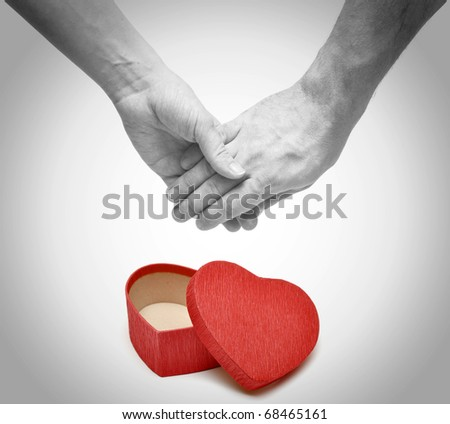 A young couple holding hands on white background. Love, care, health themes. - stock photo