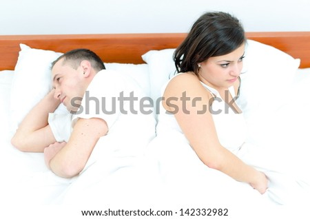 A young couple in bed having problems - stock photo