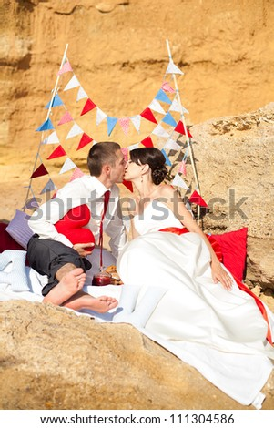 A young couple in love bride and groom posing on the beach by the sea in their wedding day in summer. Enjoy a moment of happiness and love. - stock photo