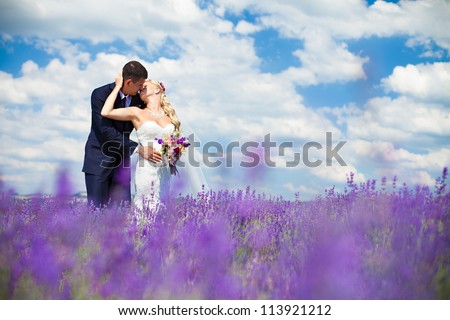 A young couple in love bride and groom, wedding day in summer. Enjoy a moment of happiness and love in a lavender field. Bride in a luxurious wedding dress on a background bright blue sky with clouds. - stock photo