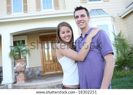 A young couple in love in front of their new home