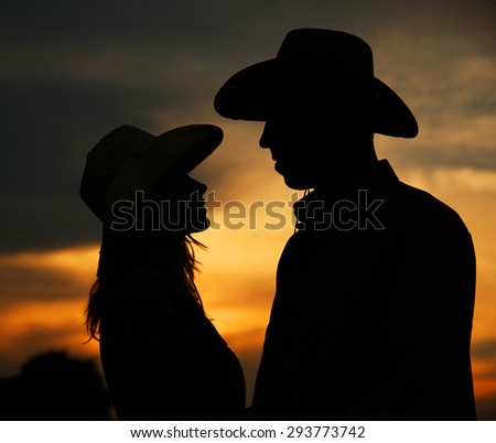 a young couple in love silhouette in cowboy hats