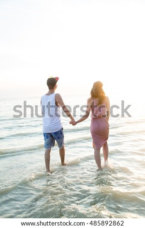 A young couple in love walks on the beach at sunset holding hands. The concept of love and affection, a date