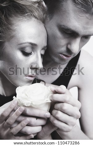 A young couple in love with a white rose and silver make-up