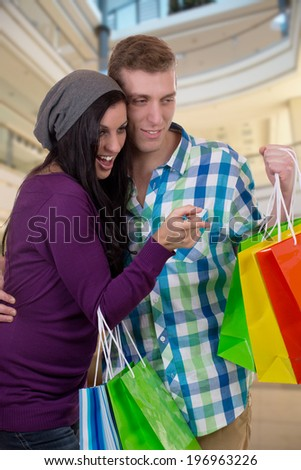 A young couple is finding something while shopping in a mall