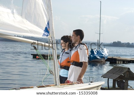 A young couple is standing next to a sailboat.  They are smiling and looking away from the camera.  Horizontally framed shot. - stock photo
