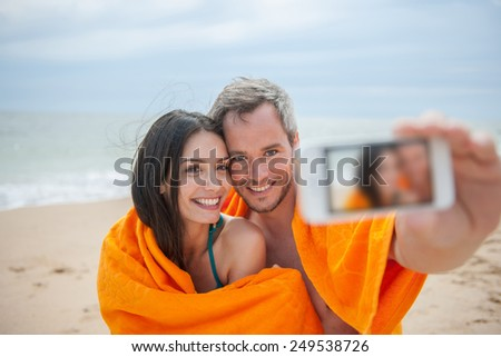 A young couple is taking a selfie at the beach. Focus on the couple