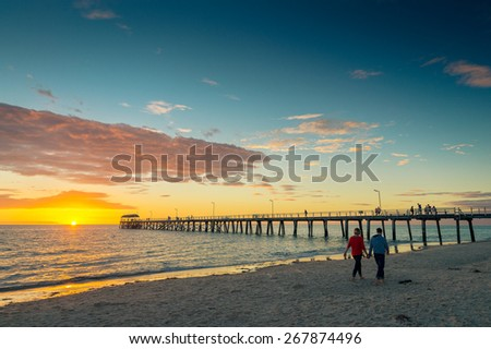 A young couple is walking along the beach at sunset and holding hands - stock photo