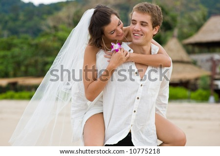 A young couple just married on a tropical beach - stock photo