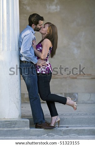 A young couple kissing during an embrace. - stock photo