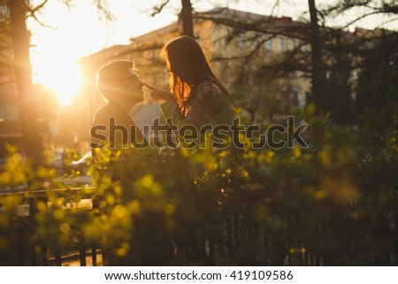 A young couple kissing in front of their new home. recently we bought a house and are happy. a new home for the newlyweds, took out a mortgage. A new life, a child soon. Hipster couple - stock photo