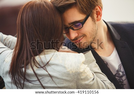A young couple kissing in front of their new home. recently we bought a house and are happy. a new home for the newlyweds, took out a mortgage. A new life, a child soon. Hipster couple
