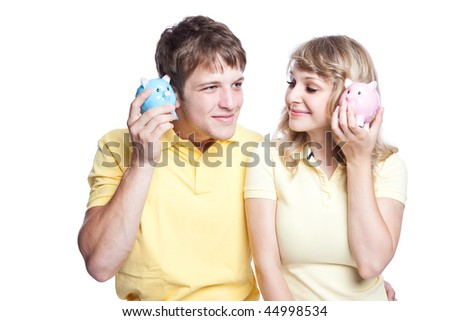 A young couple listening to their piggy banks, can be used for finance or saving concept - stock photo