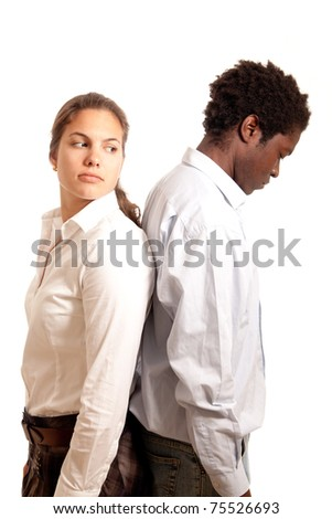 a young couple looking sad standing with their back to each other - stock photo