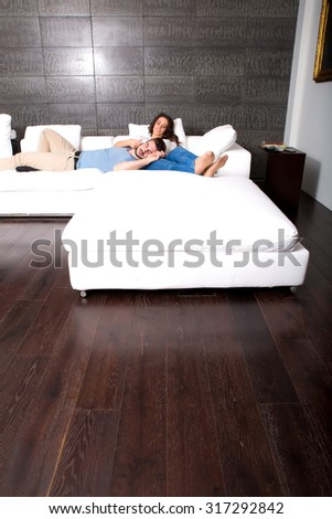 A young couple lying together on the sofa at home in the living room.  - stock photo