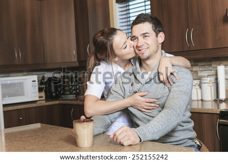 A Young couple posing in their kitchen - stock photo