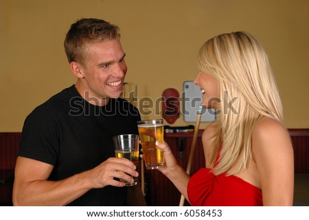 A young couple proposing a toast in a nightclub - stock photo