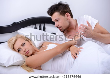 A young couple, quarreling, lying in bed in her bedroom - stock photo